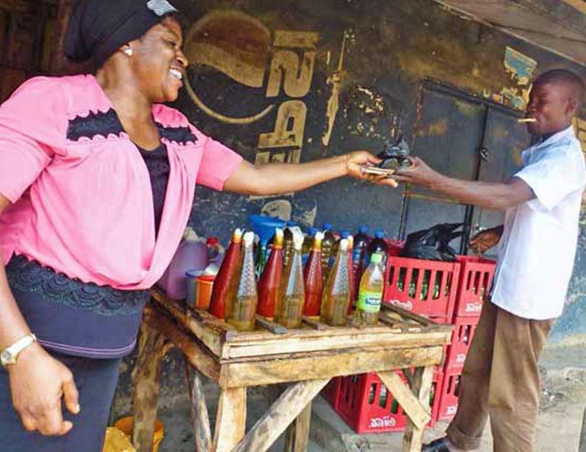 Chioma Dike est une femme d'affaires assidue. Ici, elle vend de l'huile de palme à un client. csi