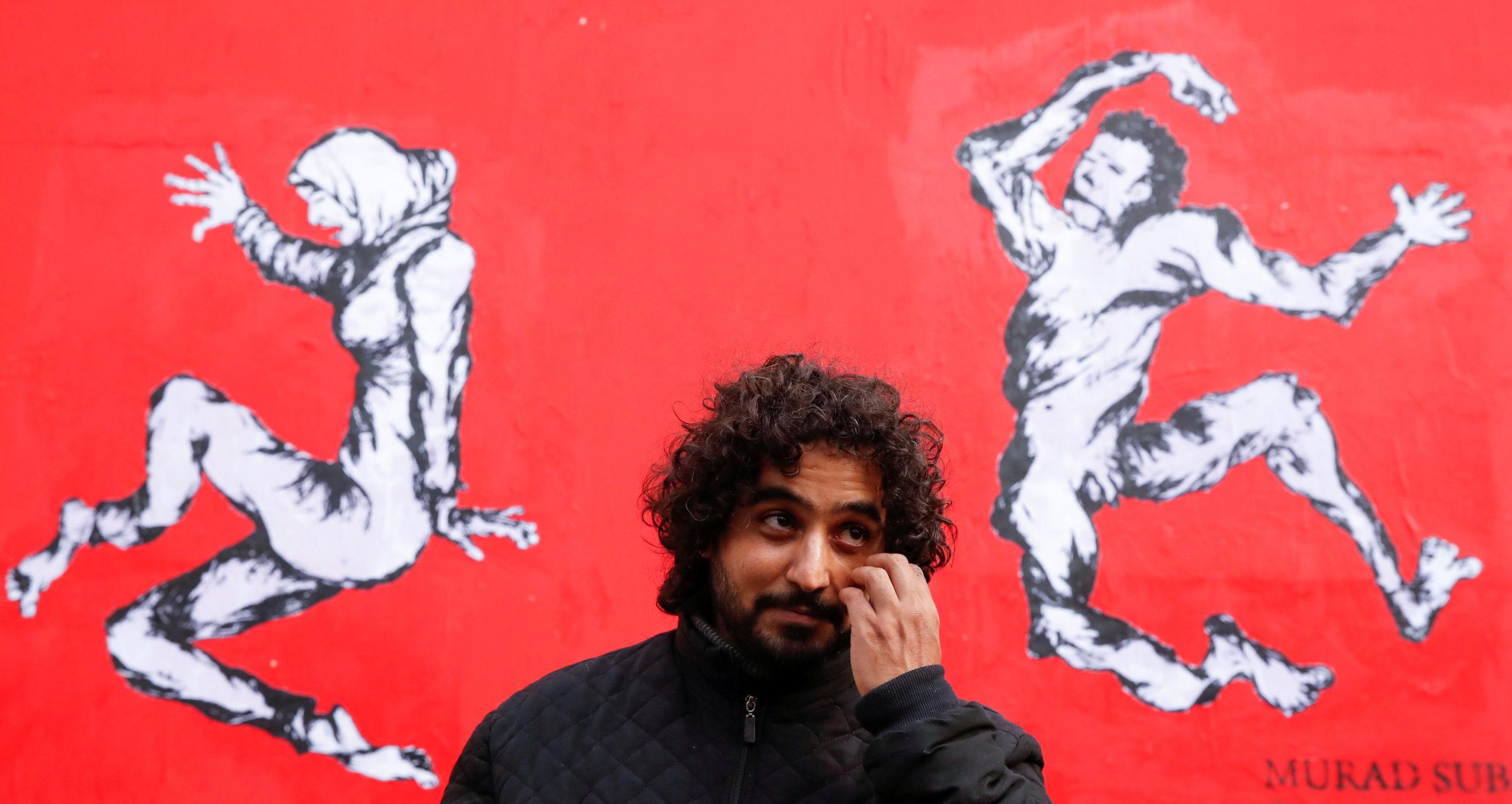 """""""Sur le corps des Yéménites, passent la guerre, l'hypocrisie internationale et les armes"""" : l'artiste Murad Subay, surnommé le """"Banksy du Yémen"""", a dévoilé mardi à Paris une fresque murale de trois mètres de haut (en photo) qui dénonce, sur fond rouge, la vente d'armes françaises à la coalition qui intervient militairement dans son pays. /Photo prise le 19 novembre 2019/REUTERS/Christian Hartmann"""