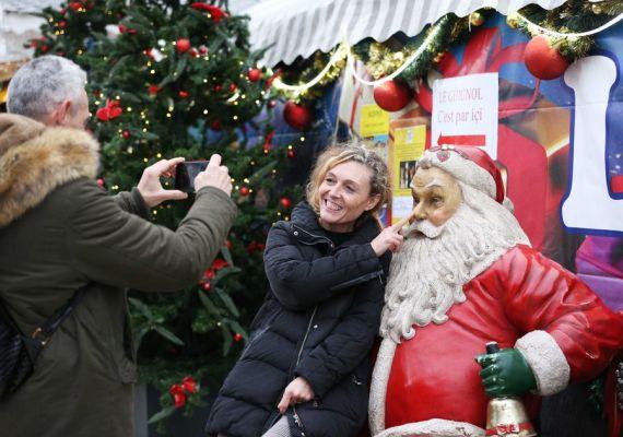 Une visiteuse avec une sculpture du Père Noël au marché de Noël dans le Jardin des Tuileries à Paris en France. (Xinhua/Gao Jing)