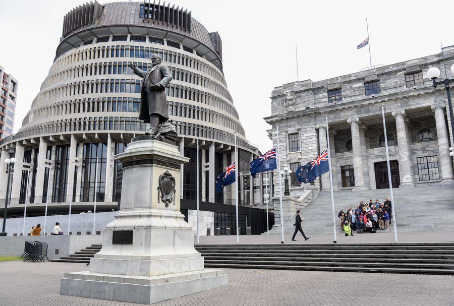 Des drapeaux de la Nouvelle-Zélande flottent en berne devant les édifices du Parlement pour rendre hommage aux victimes de l'éruption volcanique de White Island à Wellington, en Nouvelle-Zélande, le 16 décembre 2019. (Xinhua/Guo Lei)