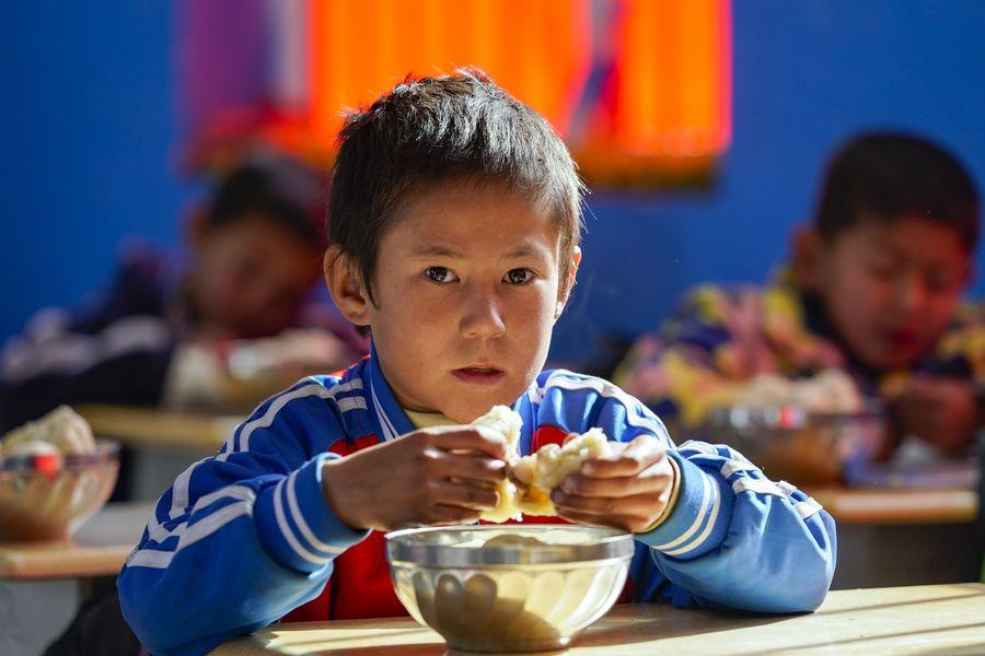 Un écolier en première année prend un déjeuner gratuit sur le nouveau campus d'une école à Daliyaboyi, bourg du district de Yutian, dans la région autonome ouïgoure du Xinjiang (nord-ouest), le 19 novembre 2019. (Photo : Shen Bohan)